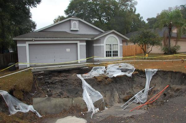 Sinkhole in front of house. Photo from USGS